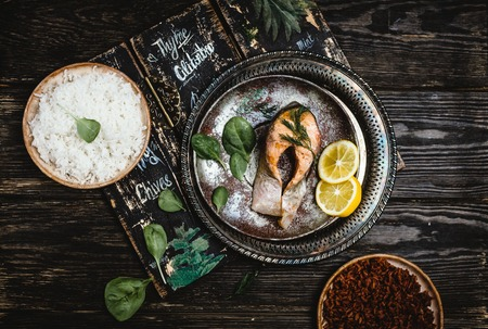Top view of baked salmon steak with lemon on rustic metal tray with rice side dish Stock Photo - 93126992