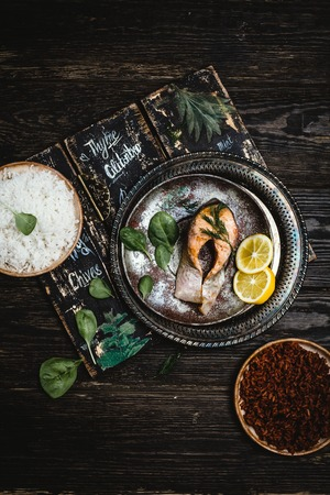 Top view of baked salmon steak with lemon on rustic metal tray with rice side dish Stock Photo - 93126994
