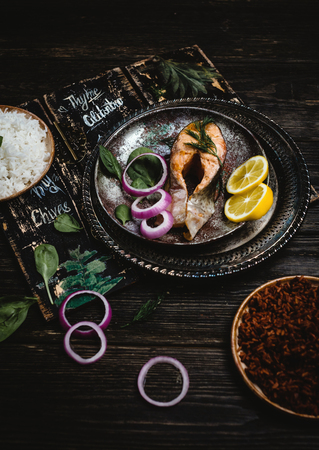 Baked salmon steak with lemon and onion on rustic metal tray with rice side dish