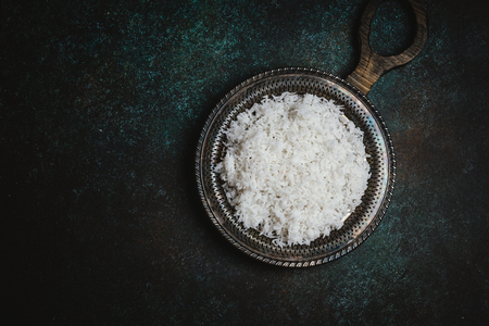 cooked white rice on rustic metal tray on dark table Stock Photo