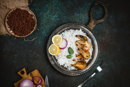 cooked shrimps with lemon and onion on rustic metal tray with rice side dish on dark table