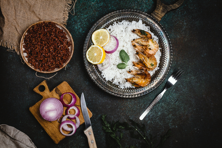 cooked shrimps with lemon and onion on rustic metal tray with rice side dish on dark table Stock Photo - 93127003
