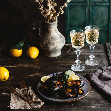 Cooked mussels with shells served on plate with two glasses of white wine