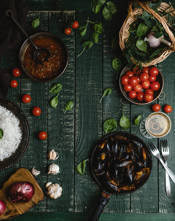 Top view of cooked mussels with shells served in pan with tomatoes, herbs and wine