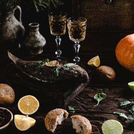 Gebakken vis met citroen en kruiden op een houten bord met witte wijnglazen Stockfoto - 93127039