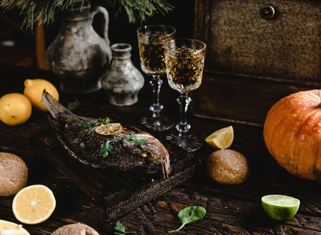 Baked fish with lemon and herbs on wooden board with white wine glasses