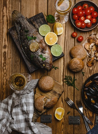 Top view of assorted seafood and baked fish with bread, tomatoes and white wine