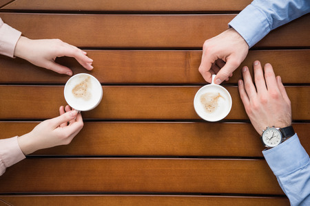 man and woman sitting at table with coffee Stock Photo