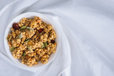plate with homemade granola on white tablecloth 免版税图像