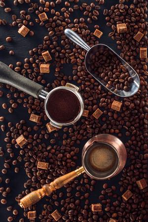 roasted coffee beans, scoop, coffee tamper, coffee pot and brown sugar on black