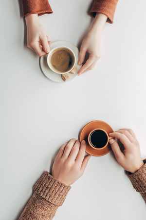 male and female hands with cups of coffee on white