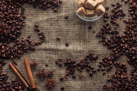 Chicchi di caffè tostati con bastoncini di cannella, anice stellato e zucchero di canna in una ciotola di vetro Archivio Fotografico - 93281005