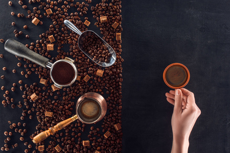person holding cup of coffee and roasted coffee beans with coffee pot, scoop and sugar