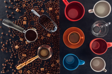 roasted coffee beans, scoop, coffee pot, coffee tamper and cup of coffee with empty cups on black