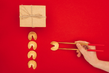 woman taking chinese fortune cookie with chopsticks, Chinese New Year concept Stock Photo