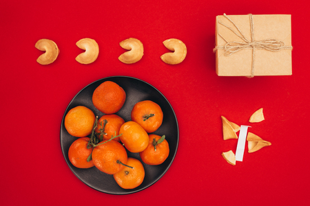chinese fortune cookies and tangerines on red surface as chinese new year composition