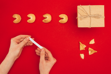 woman opening fortune cookie over red surface with handmade giftbox, Chinese New Year concept
