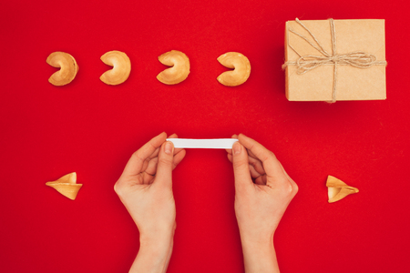 woman opening fortune cookie over red surface, Chinese New Year concept