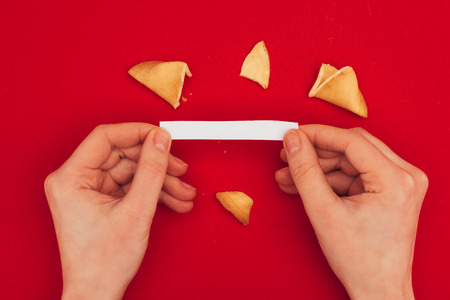woman opening traditional fortune cookie, Chinese New Year concept Archivio Fotografico