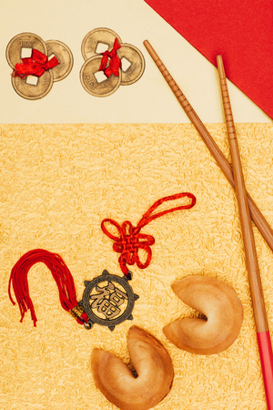 chinese talismans with fortune cookies and chopsticks on golden surface, Chinese New Year concept Stock Photo