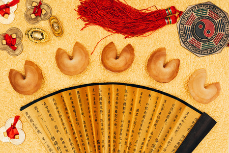 chinese talismans and fortune cookies on golden surface, Chinese New Year concept