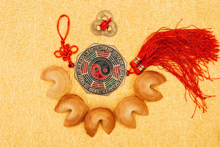 chinese talisman surrounded with fortune cookies on golden surface, Chinese New Year concept Stock Photo
