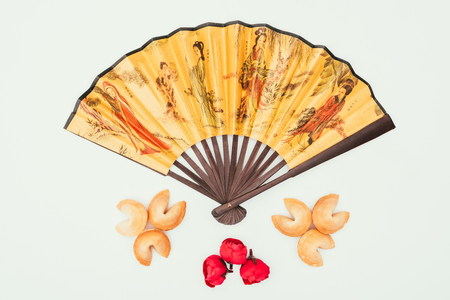 traditional chinese handheld fan with flowers and fortune cookies isolated on white