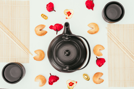 top view of chinese teapot with flowers and fortune cookies Stock Photo