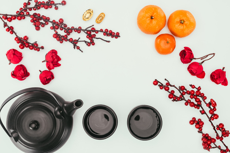 top view of chinese new year composition with tea and branches of berries