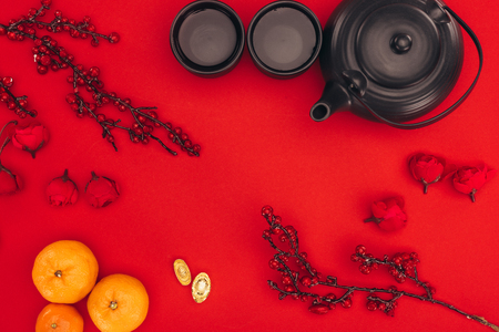 chinese new year composition with tea and branches of berries on red