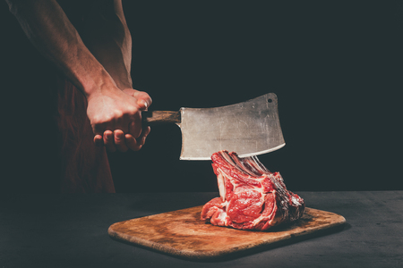 butcher cutting raw meat with cleaver