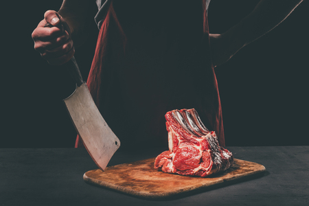butcher with cleaver and raw meat Stock fotó