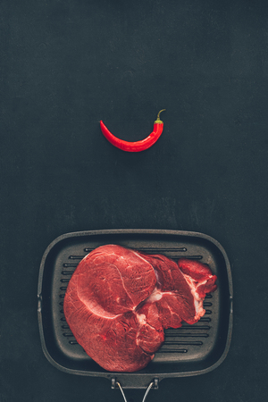 raw steak on grill pan with chili pepper