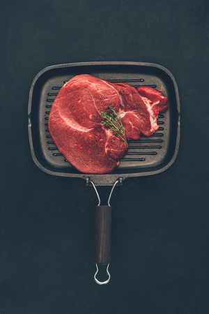 raw steak with herb on grill pan