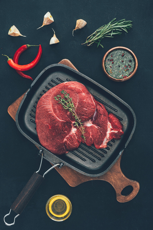 raw steak on grill pan with various spices around