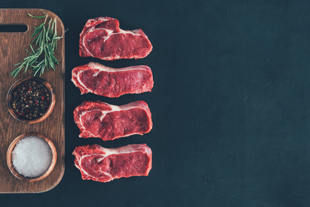 raw steaks in row with spices on wooden board Stock Photo