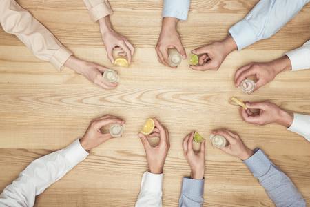 Amis mains avec des coups de tequila sur la table en bois Banque d'images - 93209941