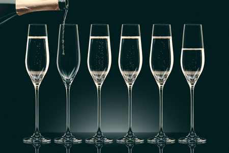pouring champagne from bottle into six transparent glasses