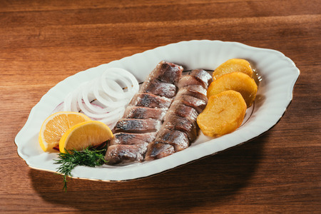 Herring fish pieces with lemon, onion