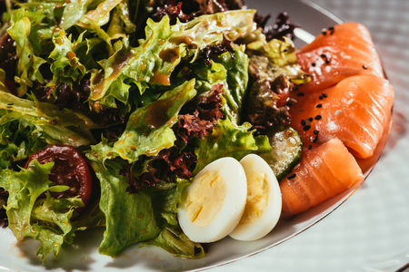 fresh salad with vegetables, eggs and salmon served on white plate