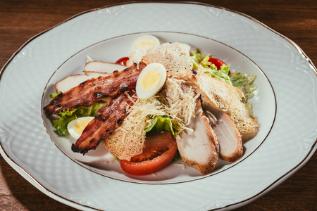 delicious salad with chicken meat, bacon, eggs and cheese