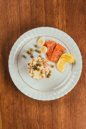 Russian salad on plate with scattered peas Stockfoto
