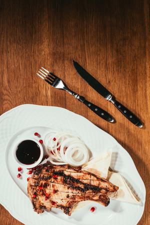Filete a la parrilla en un plato con aros de cebolla y platillo Foto de archivo - 93299408