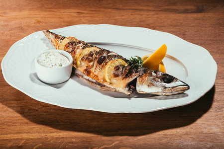 Baked fish with lemon and herbs on white plate Standard-Bild