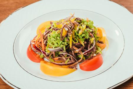 fresh vegetables sliced on white plate Standard-Bild