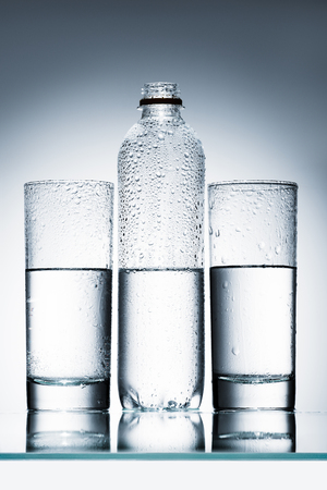 plastic bottle and glasses of clean water in row Stock Photo