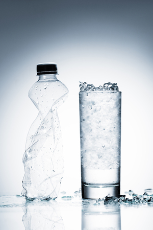 glass of cold water with ice and crumpled plastic bottle on reflective surface