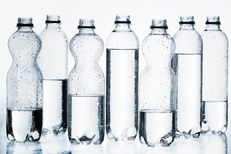 plastic bottles of water in row isolated