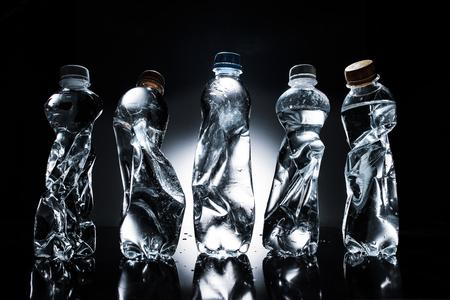 various crumpled plastic bottles of water in row