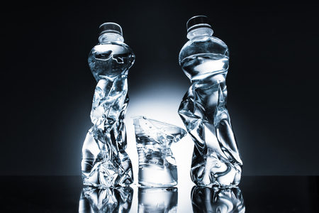 still life with crumpled plastic bottles and water and cup of water Stock Photo